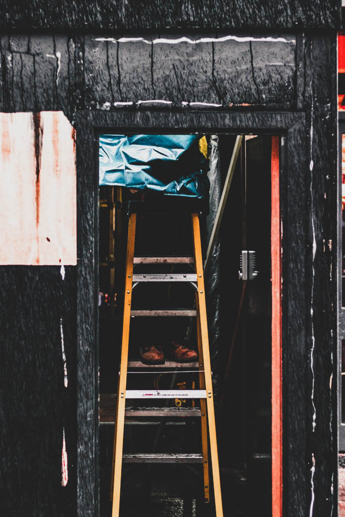 photography of person on A-frame ladder near door