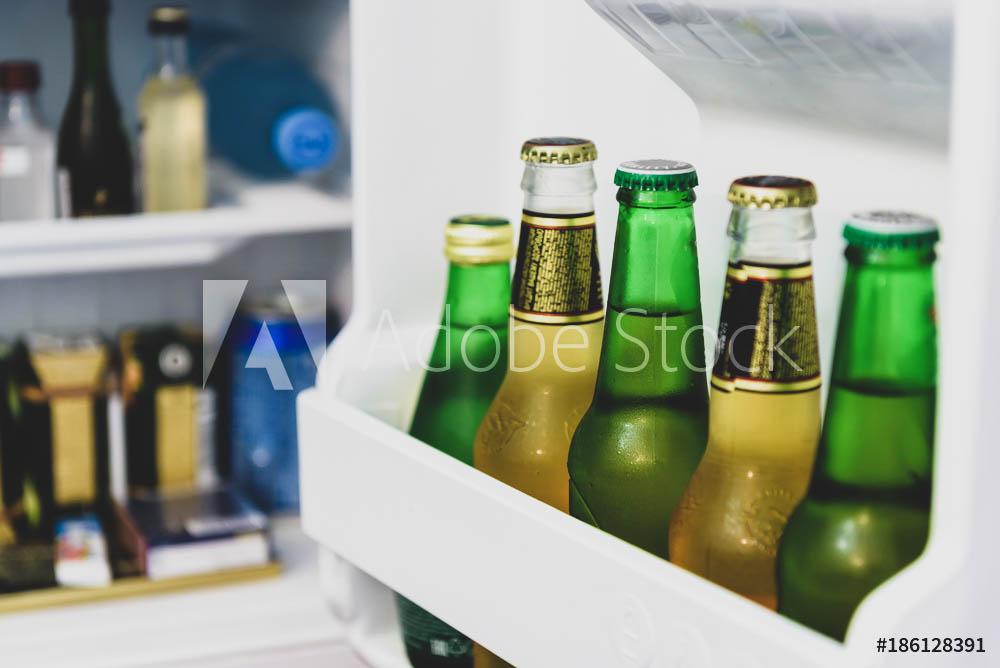 Mini fridge full of bottles in a hotel room