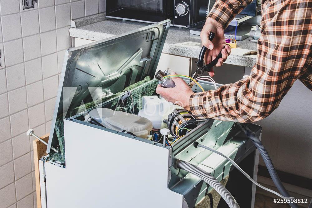 People in technician jobs. Appliance repair technician or handyman works on broken dishwasher in a kittchen. Laborer is changing the heating element.