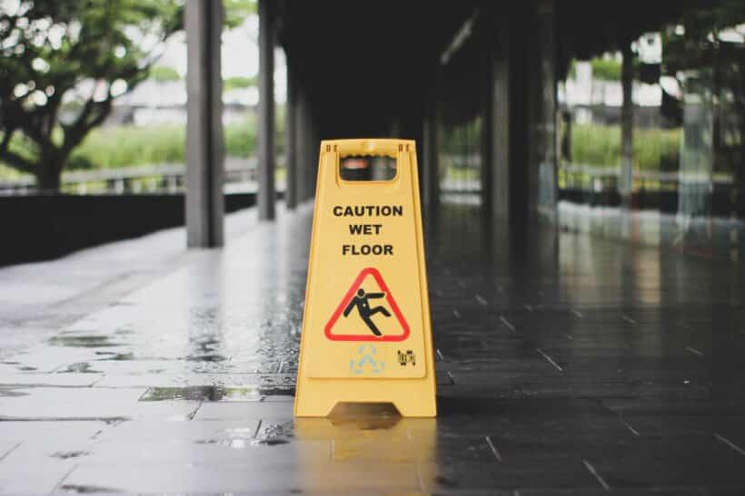 yellow Caution wet floor signage on wet pavement